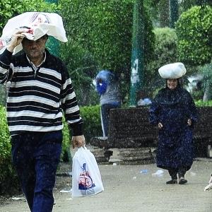 كارتون ونايلون وكاب.. حيل المصريين لمواجهة الأمطار