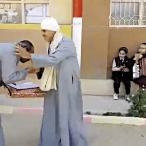 مدير مدرسة يُقبِّل يد عامل وسط تصفيق الطلاب