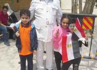 بالصور.. الأطفال يوثقون مشاركتهم بالاستفتاء مع رجال الشرطة في الجيزة