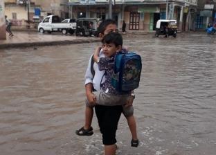 صور.. طفل يحمل شقيقه ويسبح في مياه الأمطار للوصول لمدرسته ببرج البرلس