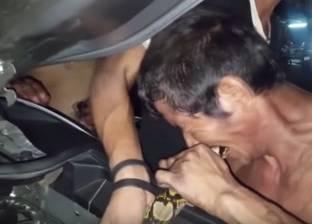 بالفيديو| رجل يعض ثعبانا ليبعده عن محرك سيارة في تايلاند