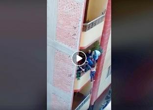 بالفيديو| مواطن يحاول إلقاء زوجته من «البلكونة» في فيصل.. «مشهد مرعب»
