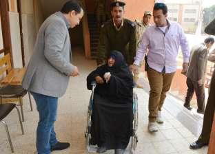 مستشار يساعد سيدة مسنة على للإدلاء بصوتها خارج اللجنة في سوهاج
