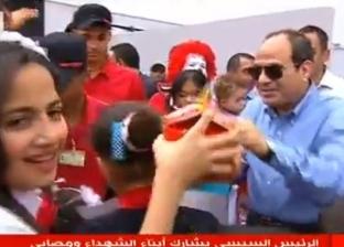 صور| السيسي يوزع وجبات طعام وحلوى وآيس كريم على أبناء الشهداء