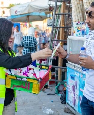 أصنع بهجة.. متطوعون أقباط يوزعون ورود وشكولاته أمام معبد الأقصر
