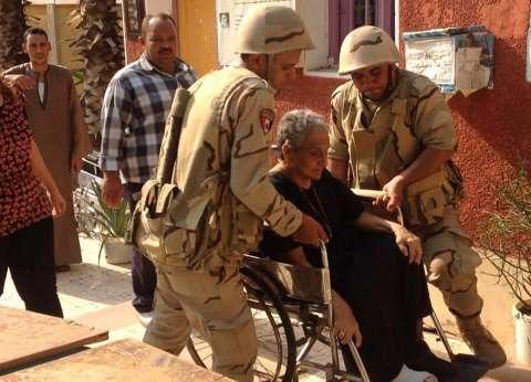 أثناء فترة الراحة.. قوات الجيش توزع مياه معدنية على الناخبين وتوفر مقاعد للجنود بالطالبية