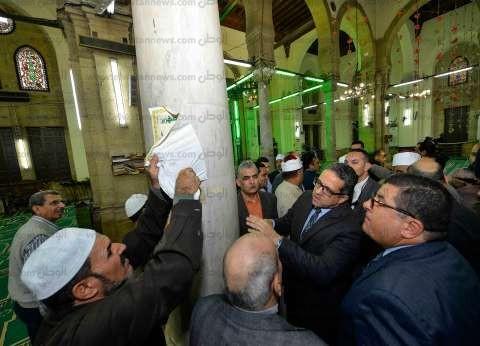 بالصور| العناني يزيل الملصقات عن حائط مسجد الرفاعي الأثري
