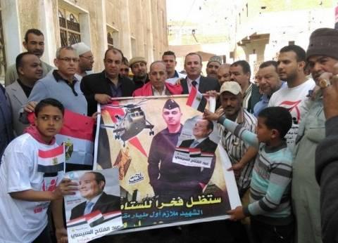 """أهالي """"الستاموني"""" بالدقهلية يرفعون صور شهدائهم أمام اللجان الانتخابية"""