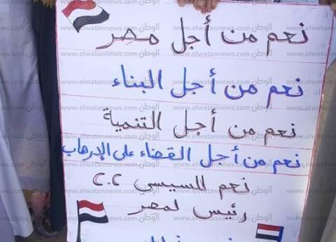 """طفلة بالبحيرة ترفع لافتة تأييد لـ""""السيسي"""": من أجل البناء والتنمية"""