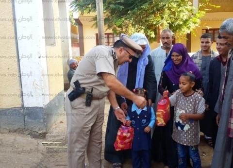 بالصور| ضباط أمن أسيوط يصطحبون أبناء الشهداء لمدارسهم