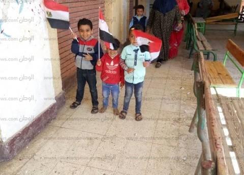 بالصور| أم تصطحب صغارها الثلاثة في جولة انتخابية بالأعلام: مبسوطة بيهم