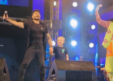 تامر حسني يغني مع طفل معافى من السرطان في نادي الشمس