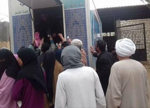 بالصور| سيارة الخدمة الوطنية تبيع السلع الغذائية المدعومة لأهالي قرية بالفيوم