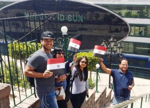 البواخر السياحية تطلق صافرات وبعض السياح يرفعون أعلام مصر بأسوان