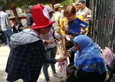 موظفون ومتطوعون يساعدون المسنين في الإدلاء بأصواتهم بالاستفتاء