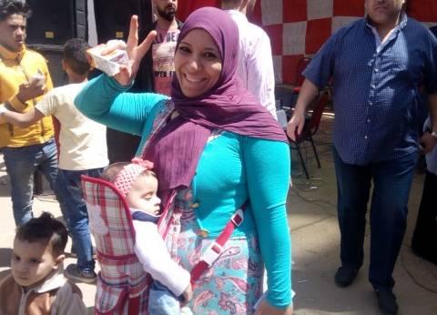 سيدة تصطحب أطفالها للمشاركة في الانتخابات لتعلمهم حب الوطن