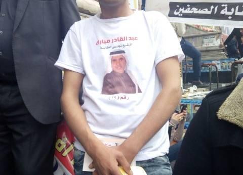 """أنصار عبدالقادر مبارك بـ""""تي شيرتات"""" عليها صورته وينتشرون أمام السرادق"""