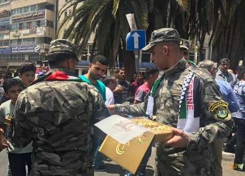 الشرطة الفلسطينية توزع الحلوى ابتهاجا بإزالة الحواجز بالأقصى