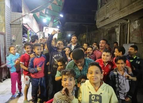 بالصور| أطفال بولاق أبوالعلا يلتقطون صورا تذكارية مع أحمد عز