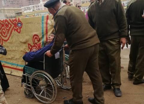 صور| شرطي يحمل مسنة لتدلي بصوتها في إحدى لجان شبرا الخيمة