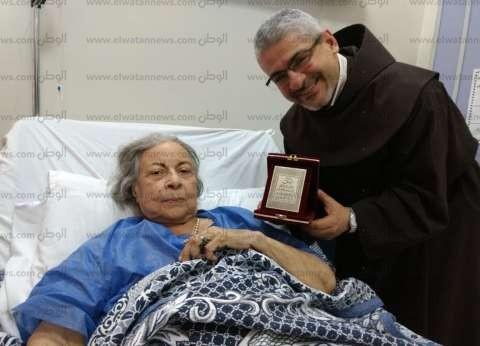 بالصور| الأب بطرس دانيال يُكرم آمال فريد بعد تعافيها بأحد المستشفيات
