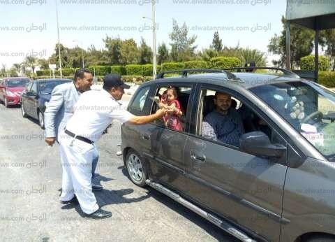 بالصور| أمن نفق الشهيد أحمد حمدي يوزع الورود على المواطنين