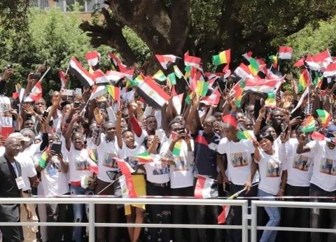 """بـ""""تي شيرت السيسي وكوندي"""".. طلبة """"عبدالناصر"""" يستقبلون الرئيس في غينيا"""