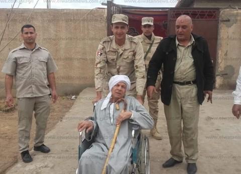 رجال الشرطة والجيش يساعدون كبار السن للوصول إلى لجانهم بكفر الشيخ