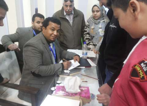 """""""إسماعيل"""" خطاط يكتب أسماء زوار معرض الكتاب على البطاقات"""
