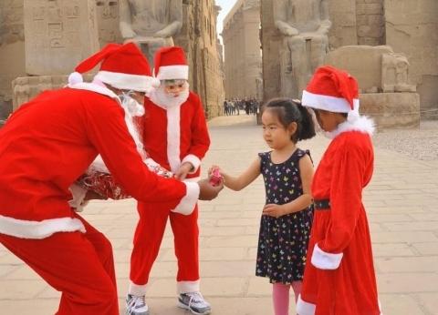 """""""بابا نويل"""" يوزع الهدايا الفرعونية والورود على السائحين بمعبد الأقصر"""