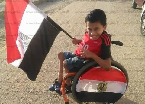 «كريم» زين كرسيه «المتحرك» بأعلام مصر لتشجيع المنتخب باستاد برج العرب