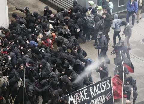 بالصور  اشتباكات بين مناهضي ترامب والشرطة الأمريكية.. وحرق العلم الأمريكي