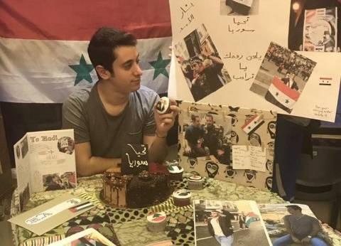 """على أضواء القنابل.. كعكة عيد ميلاد """"هادي"""" بأعلام سوريا وصورة بشار"""
