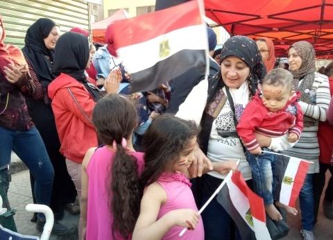 سيدة ترقص مع طفلتيها ورضيعها عقب الإدلاء بصوتها في لجنة بشبرا