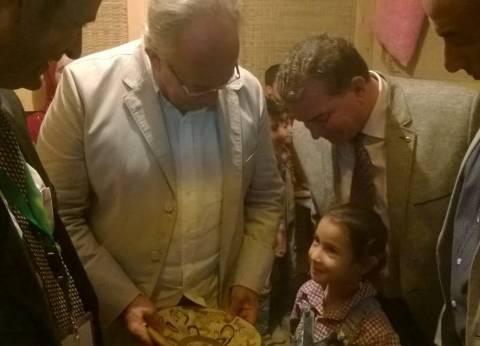 بالصور| وزير التنمية المحلية يشتري طبق فضة من تلميذة بـ50 جنيها