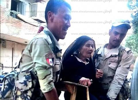 جنديان يحملان عجوزا للإدلاء بصوتها في انتخابات الرئاسة ببني سويف