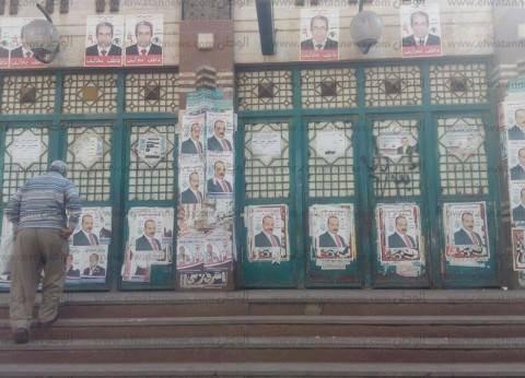 """مدخل مترو عزبة النخل يتحول لـ""""لوحة مشوهة"""" بلافتات مرشحي النواب"""