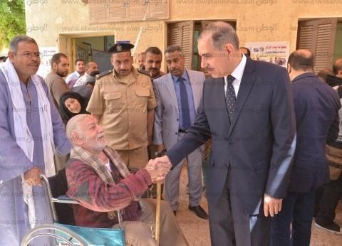 بالصور| محافظ أسيوط يصطحب مسنا للجنة للإدلاء بصوته في الاستفتاء