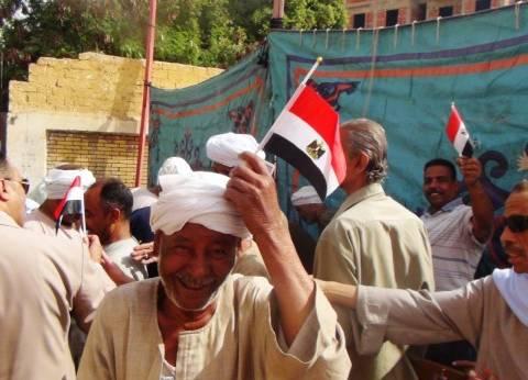 """رجال الشرطة توزع """"علم مصر"""" على الناخبين في أسوان"""