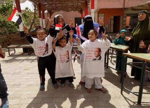 """سيدتان تصطحبان أطفالهن بملابس عليها علم مصر..""""لكي يحبوا الوطن"""" بالفيوم"""