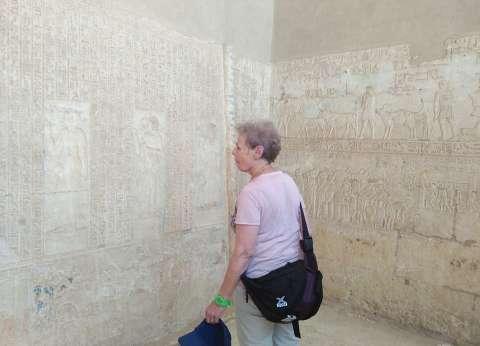 سائحة تخلع قبعتها وتنحني أمام مقبرة كبير كهنة تونا الجبل في المنيا