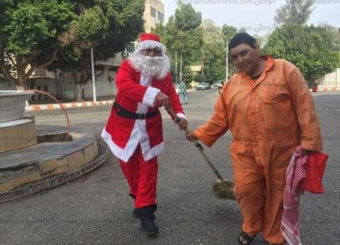 «بابا نويل» يكنس شوارع قنا ويوزع الهدايا على المارة