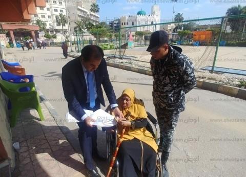 رئيس لجنة بمركز شباب سموحة في الإسكندرية يساعد مسنة للاستفتاء