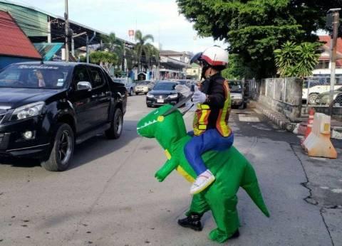 """سائقون في تايلاند يتفاجأون بـ""""ديناصور"""" ينظّم حركة المرور"""