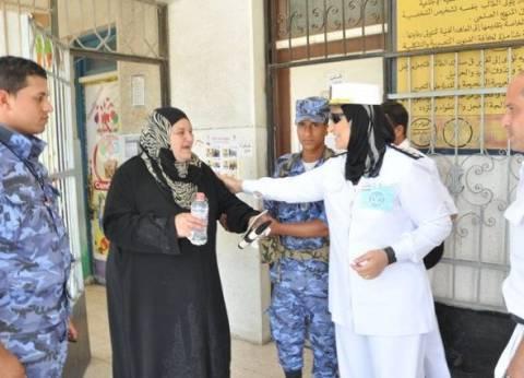 الشرطة النسائية توزع زجاجات مياه على الناخبين في بورسعيد