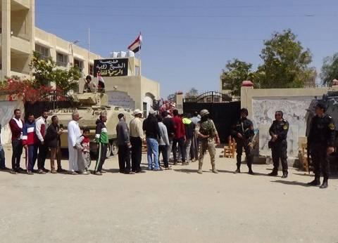 بالصور| أطفال الشيخ زويد يرفعون أعلام مصر أمام اللجان الانتخابية
