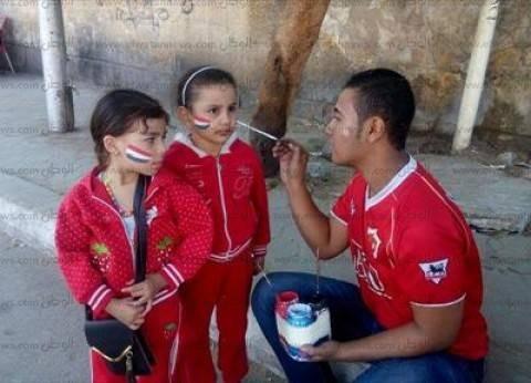 """شاب يرسم """"علم مصر"""" على وجوه الأطفال أمام لجان السيدة زينب.. """"الرسمة بجنيه"""""""