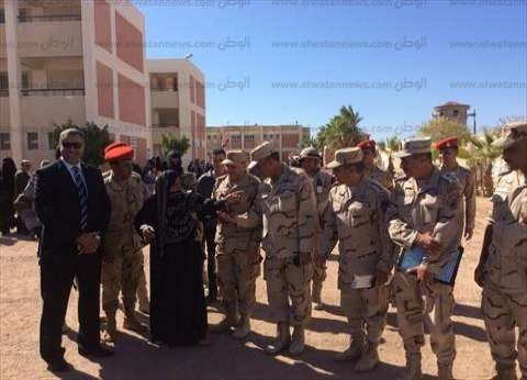 قائد الجيش الثاني ومدير أمن بورسعيد يقبلان يد ورأس سيدة عجوز أثناء تفقد اللجان