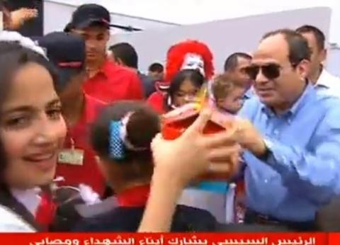 صور  السيسي يوزع وجبات طعام وحلوى وآيس كريم على أبناء الشهداء