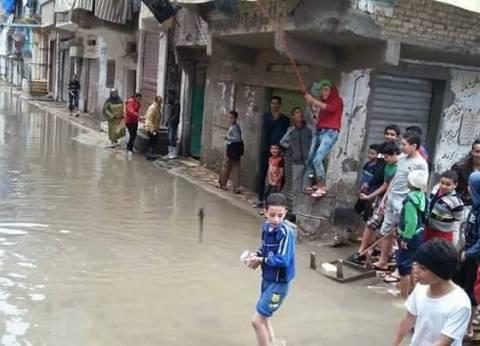 بالصور| مسابقة لصيد الأسماك في مياه الأمطار بشوارع الإسكندرية